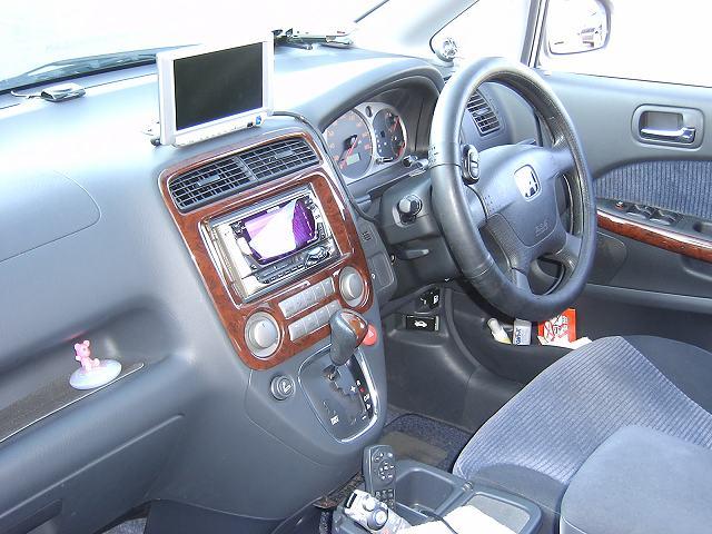運転席周りをパチリ<br /> <br /> シフトレバーをオデッセイのものを流用されていたと思います。<br /> 違和感無くていいですね。木目好きの方は参考にされてはいかがでしょう。<br /> <br /> オプションの灰皿のところにつけるテーブルもカップホルダーがついていて便利そう・・・<br /> <br /> うちのレカロ付きストでも使えるかな?