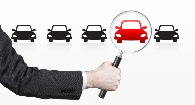 横にならんでいる黒の車の中から虫眼鏡を使って赤いクルマを拡大