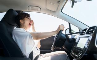運転中の女性があくびをしている画像