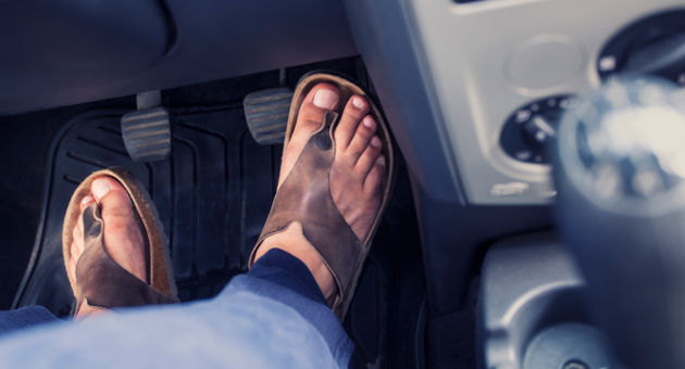 サンダルを履いた男性の足と車のブレーキの画像