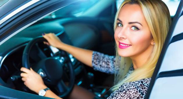 運転席に座りながら笑顔を見せる美女の画像