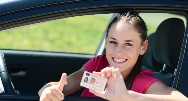 運転席に座る免許証を持って笑顔の女性の画像