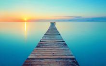 きれいな湖と橋に注ぐ夕日の画像