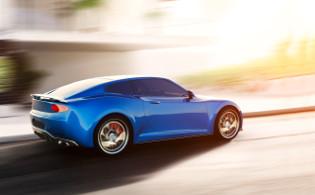 舗装道路上を青いスポーツカーが走行している画像