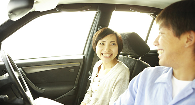 カップルが車内で談笑している画像