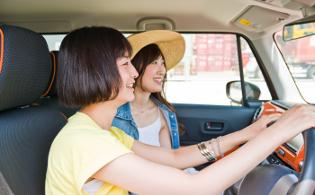 女性二人がドライブしながら談笑している画像