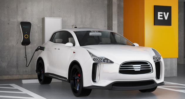 駐車場で充電中の白ハイブリッド車