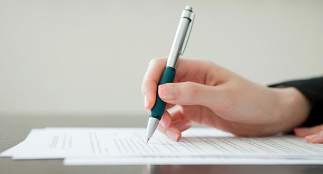 手と紙とペンの画像