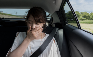 車内で車酔いしている女性