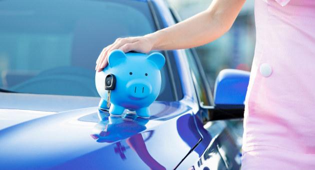キレイな青い車のフロントに乗っているブタの貯金箱とそれに手を置く女性