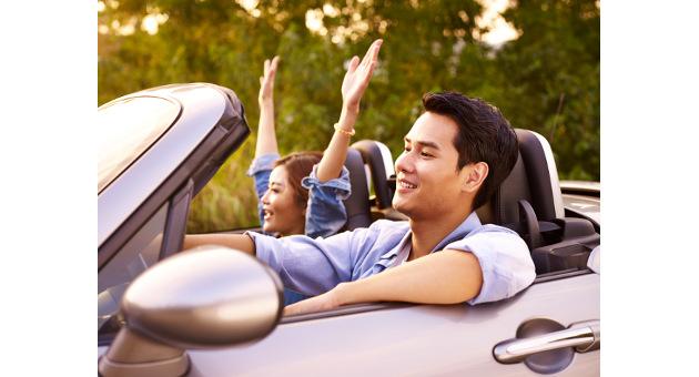 オープンカーでドライブを楽しむ男女