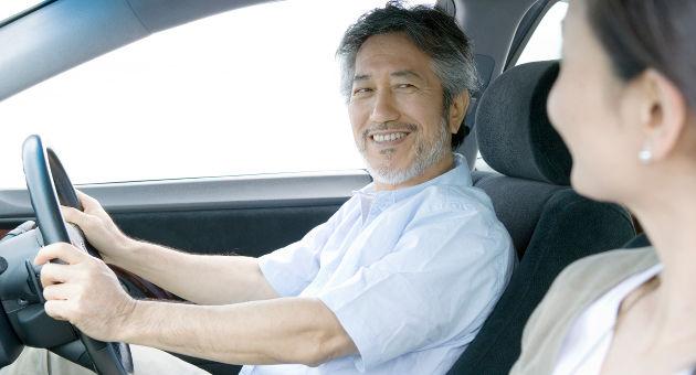 ドライブ中、助手席の女性に笑いかける運転席に座る男性