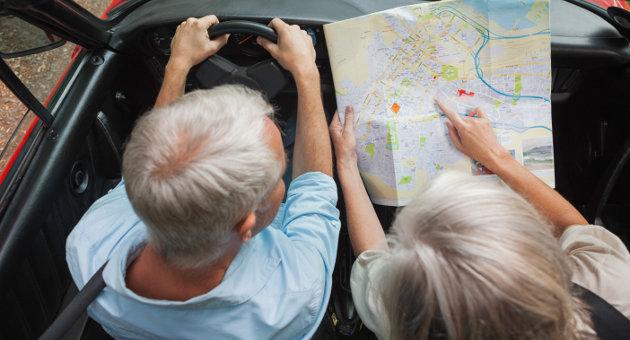 ドライブ中、地図を広げて相談中の年配カップル