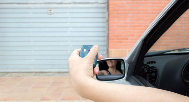 車庫入れをするためにガレージをセンサーで開けようとする女性