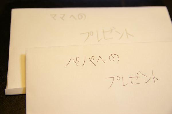 手作りの封筒に書かれたパパとママへのプレゼントの文字