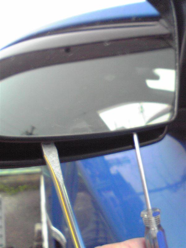 ミラーの下からドライバーを差し込んで、ミラー裏の下側クリップ2箇所を外し、ミラーを持ち上げて引き下げてミラー裏の上側フックを外します。