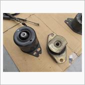 左がエンジンマウント、右がエンジンロアマウント。<br /> <br /> エンジンマウントは、エンジンを吊っているほうのマウントだそうです。<br /> <br /> 中心の軸周囲がゴムになっているそうですが、芯をぐっと左右に押すとゴムにわずかな亀裂。<br /> <br /> そして、要約するとエンジンを吊ると芯がぐっと下に伸びてきてしまうとへたっていると判断するそうです。<br /> <br /> エンジンロアマウントも中央に亀裂が入っています。