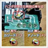 【LED取付け作業-1】<br /> 盛ったハンダにコテを当て、<br /> ハンダが溶けたところにLEDの片足を付けます。<br /> この作業がメインです。<br /> <br /> LEDには極性があるので、向きに注意です。<br /> <br /> 草心LEDの場合は、<br /> チップに欠けがある方がカソード(-側)になるので、<br /> 基盤の「 K 」と書いてある方に合わせます。<br /> カソード:英Cathode、独Kathode<br /> <br /> チップによってはLED裏側に、<br /> 三角のダイオードマークあるので、<br /> 三角の向きをカソード側に合わせます。<br />