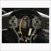 バッテリーのマイナス端子を外して暫く待つ。<br /> 待つ必要もなくエアバッグの取り外しに難儀する。<br /> <br /> 右側、下側はすんなりだが、左側が大変分かりにくい。<br /> エアバッグに手を添えて、穴からドライバーをゴソゴソ動かしていると、ピンに当たる時に手応えがあるので、その手応えを頼りにピンを押す。<br /> ピンが土台から外れればポコッとエアバッグユニットが浮き上がる。<br /> 右側のアースと黄色いコードを外すとユニットが外せる。