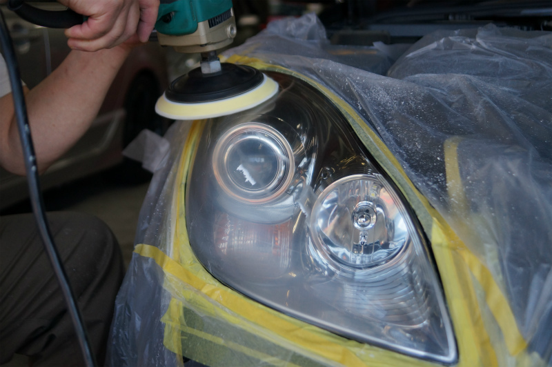 ポリッシャーでの磨き作業を終えヘッドライトコーティング+1層分のガラス系被膜の塗り込みです。