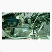 エンジンが載りました。<br /> 配線、燃料ホースなどを繋ぎ、オイルを入れます。<br /> フライホイールを何回転かさせ、ある程度オイルを循環させます。プラグを抜いておくと楽です。ある程度回したらセルで回してもいいです。セルで回すときはキルスイッチをオフにしておくように。<br /> <br /> ついに<br /> キルスイッチをオンにして緊張のエンジン始動です。<br /> が、ここで問題発生。<br /> オイル循環を念入りにやりすぎたためかバッテリーが上がりかけてしまいました。<br /> クラッチの調整もまだ済んでいないので押しがけもできません。困った。<br /> しかしこの後奇跡的にバッテリーが復活しました。<br /> 日頃の行いがいいからですね〜(鼻ホジ)<br /> セルが弱々しく回り、エンジンがかかりました。<br /> 自分でバラした後だとこれだけでちょっと感動します。ウレシイ…<br /> 1発目はさすがに不安定なのでアイドリングを高めにして数分エンジンをかけておきます。<br /> するとどうでしょう。以前からのガラガラ音はどこかへ消えてしまいました。素晴らしい。