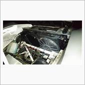 クーラントを抜いたら、ラジエター上部のインダクションボックスとエアクリーナーを外します。<br /> 厚い方のクーリングファンもフレームに干渉するので外します。<br /> ラジエターは左右のタンクに1箇所ずつ、計2箇所ナットを外せばフリーになります。<br /> アッパー側のホースをはずして、ロア側は手が入りませんが、ロースバンドだけ緩めて持ち上げます。<br /> <br /> ボンネットが前開きのため、一番力の入るポジションからアクセスするのが困難です。<br /> なので、ラジエターとエンジン間のフレームに乗って持ち上げて外しました。