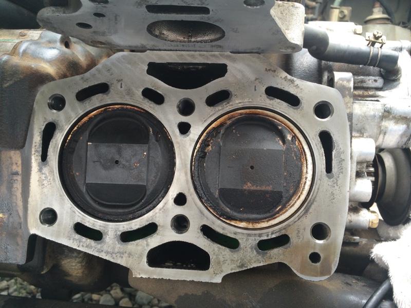 エンジン側。2気筒エンジンですね。<br /> 上に見えるのがインテーク。(マニホールドコンプ)<br /> ここのガスケットきれいにするのが大変でした。そもそも固着してて外すのも大変でした。<br /> ヘッドガスケットは、まぁ水が漏れていたくらいですから密着していることもなく、ポロっと外れてしまいました。