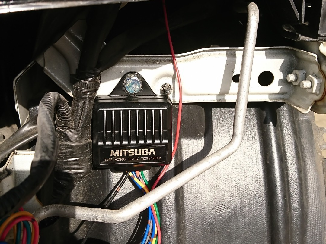 次に向かって右側ヘッドライト下に電子制御ユニットを取り付けます。<br /> <br /> そこから延びている赤コードをバッテリーのプラス端子へ、黒コードをボディーアース。<br /> 更に赤緑コードと赤燈コードをそれぞれのホーンへ接続。<br /> 残りの青コード2本は純正コネクタとボディーアースへ接続して終了です。