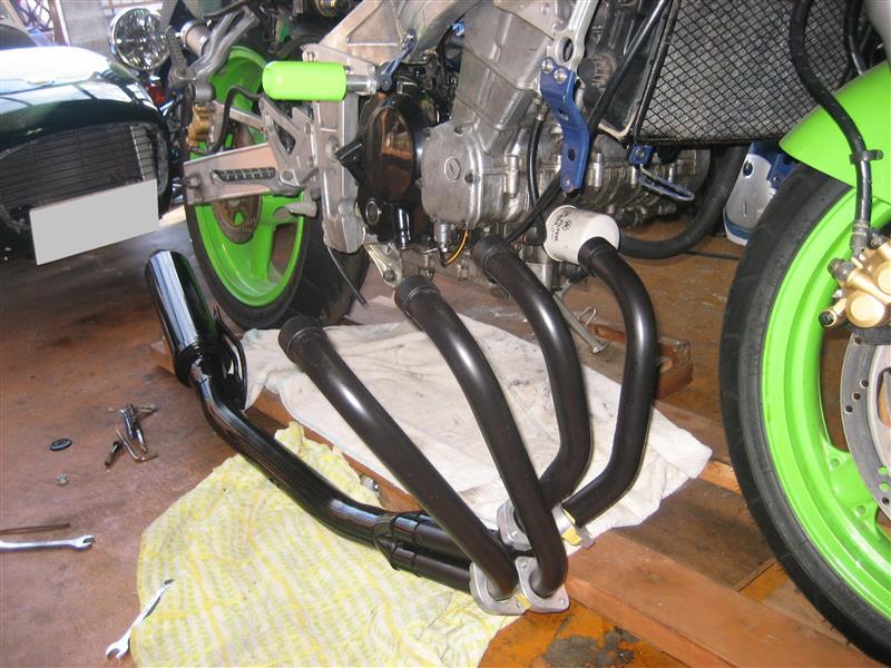 カウルを外してマフラーを装着します。<br /> 最初、ASSY状態で組付けようとしましたが、うまく装着できませんでした。<br /> なので、分解して先にサイレンサーをバイクに装着してから、エキマニを1本ずつ組付けていきました。
