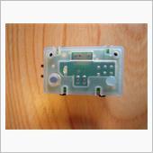 以前はタクトスイッチ部のパターンをパラで取り出して、ステアリングに増設したモーメンタリースイッチでも操作できるようにしましたが、基板のタクトスイッチをよく見るとパターンをつなぐの導電ゴムで、スイッチをオンにしたときに2.9Ωの抵抗値がありました。<br /> 増設スイッチではこの抵抗をバイパスして直結してしまうので、トラブルが発生したのかもしれません。ただ、焼損したパターンを見ると原因は基板加工、再組み立てをした時に何かをかみこんだか導通性のある液体が入り込むなどしてショートしたような感じもありました。<br /> いずれにせよ、詳細は不明ですがバイパス側にも同じくらいの抵抗をかませることにします。