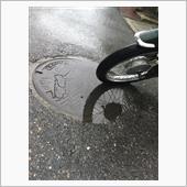 雨のマンホールと二輪車