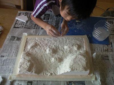 地形は歯ブラシなどで表面をデコボコにした後、絵の具で土の色を塗ります。 乾いたら、鉄道模型用のカラーパウダーを撒きます。  木工用ボンドを水で溶いて洗剤を数滴